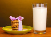 Glass of milk and cookies on wooden table on brown background — Stock Photo