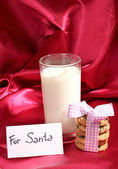 Glass of milk and cookies on red cloth background — Stock Photo