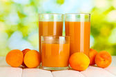 Glasses of apricot juice and fresh apricots on white wooden table on green background — Stock Photo