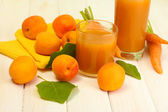 Glasses of carrot and apricot juice on white wooden table — Stock Photo