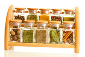 Powder spices in glass jars on wooden shelf isolated on white — Stock Photo