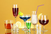 A variety of alcoholic drinks on yellow background — Stock Photo