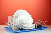 Clean dishes on stand on red background — Stock fotografie