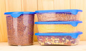 Filled plastic containers on wooden background — ストック写真