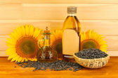 Sunflower oil and sunflower on wood background — Stock Photo