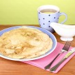 Stack of tasty pancakes on wooden table on green background - Stock Photo