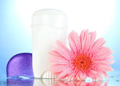 Deodorant with flower on blue background — Stock Photo