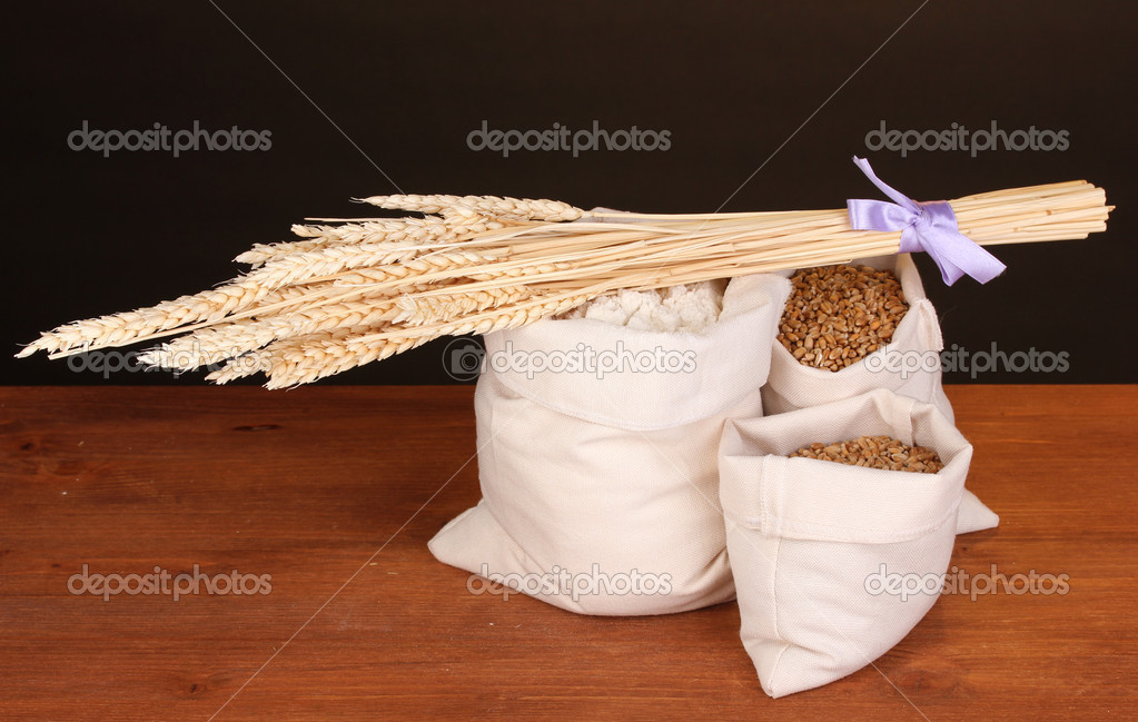 Flour and wheat grain on wooden table on dark background — Stock Photo #11547852