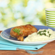 Roasted chicken leg with mashed potato in the plate and cup with milk on wooden table on bright background close-up - Stockfoto