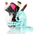 Make-up brushes in a bowl with pearl necklace isolated on white - Stock Photo
