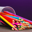 Stock Photo: Color pencils in glass on wooden table on violet background