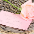 Royalty-Free Stock Photo: Beautiful rose on wicker mat with card isolated on white