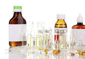 Medical bottles with medical ampoules and tablets isolated on white — Stock Photo