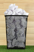 Metal trash bin from paper on grass on wooden background — Stock Photo