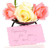 Três rosas em base de metal com cartão isolado no branco — Fotografia Stock