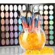 Royalty-Free Stock Photo: Make-up brushes in a bowl with stones on palette of shadows background