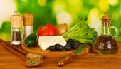 Ingredients for a Greek salad on green background close-up — Stock Photo