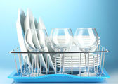 Clean dishes on stand on blue background — Zdjęcie stockowe