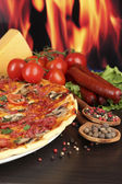Delicious pizza, salami, tomatoes and spices on wooden table on flame background — Stock Photo