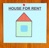 Poster about renting the house on wooden background — Stock Photo