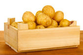 Young potatoes in a wooden box on a table on white background close-up — Stock Photo