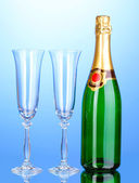 Bottle of champagne and goblets on blue background — Stock Photo