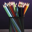 Color pencils in glass on wooden table on violet background — ストック写真