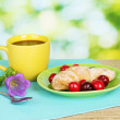 Croissant with cherries and coffee on wooden table on green background — Stock Photo #11588243