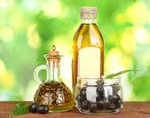 Olivolja flaska och liten karaff på grön bakgrund — Stockfoto