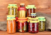 Gläser mit eingemachten gemüse und obst mit hölzernen hintergrund nahaufnahme — Stockfoto