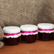 Little jars with strawberry jam on wooden background close-up - Stock Photo