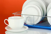 Clean dishes on stand on red background — Stok fotoğraf