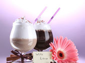 Glasses of coffee cocktail and gerbera flower on violet background — Stock Photo