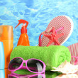 Bright beach accessories, on blue sea background - Zdjęcie stockowe