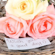 Beautiful roses on wicker mat with card close-up — Stock Photo
