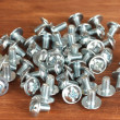 Chrome bolts on wooden background close-up - Stock Photo