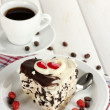 Sweet cake with chocolate on plate and cup of coffee on wooden table — Stock Photo