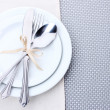 White empty plates with fork, spoon and knife tied with a ribbon on a grey tablecloth — Stock Photo #11609216