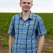 Young farmer standing near field — Stock Photo
