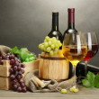 Barrel, bottles and glasses of wine and ripe grapes on wooden table on grey background — Stock Photo #11609424