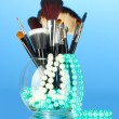 Royalty-Free Stock Photo: Make-up brushes in a bowl with pearl necklace on blue background