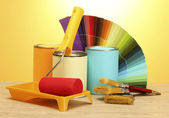 Tin cans with paint, roller, brushes and bright palette of colors on wooden table on yellow background — Stock Photo