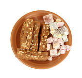 Tasty turkish delight with sherbet with nuts in the plate isolated on white — Stock Photo