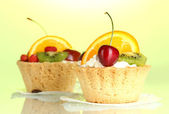 Sweet cakes with fruits on green background — ストック写真
