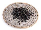 Black currant on wicker mat isolated on white — Stock Photo