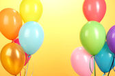 Colorful balloons on yellow background close-up — Stock Photo