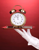 Hand in glove holding silver tray with alarm clock on red background — Stock Photo