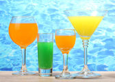 Exotic cocktails on table on blue sea background — Stock Photo