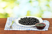 Fresh blueberries in plate with sauce boat on green background — Stock Photo