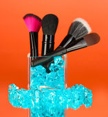 Make-up brushes in glass cup with stones on red background — Stock Photo